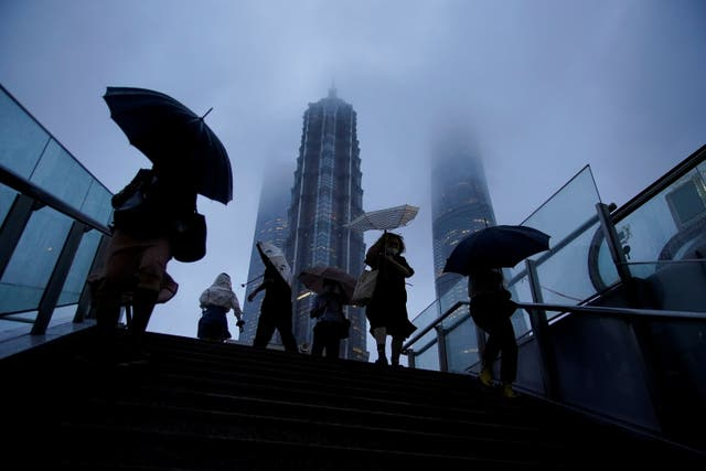 People hold umbrellas amid rainfall as Typhoon Chanthu approaches, in Shanghai, China