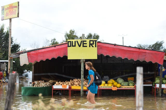 A woman walks past a fruits and vegetables stall in a flooded street in Codognan, in the Occitanie region of southern France, following heavy rains