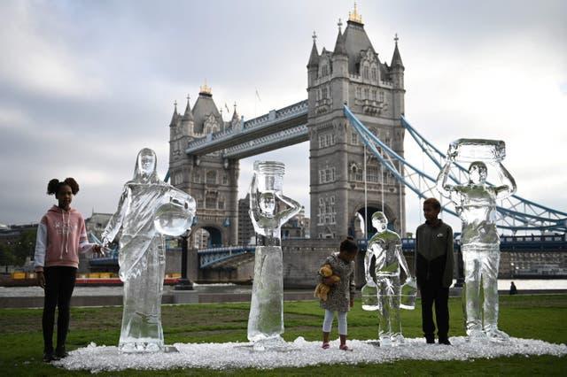 チャリティーウォーターエイドで水を集める人々を描いた氷の彫刻でポーズをとる子供たちは、水の脆弱性とロンドンの気候変動による脅威を示しています