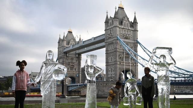 Crianças posam ao lado de esculturas de gelo que retratam pessoas coletando água para a instituição de caridade Water Aid para mostrar a fragilidade da água e a ameaça representada pela mudança climática em Londres