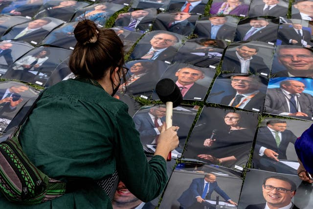 An activist places photos of German politicians outside the Bundestag in protest against human rights violations at Europe's borders