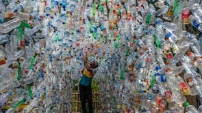 An Indonesian activist from ECOTON (ecological observation and wetland conservation) prepares an installation made with used plastic, 包括 4,444 bottles, collected from the river in Gresik to raise public awareness of plastic waste in rivers and oceans