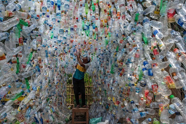 An Indonesian activist from ECOTON (ecological observation and wetland conservation) prepares an installation made with used plastic, including 4,444 bottles, collected from the river in Gresik to raise public awareness of plastic waste in rivers and oceans