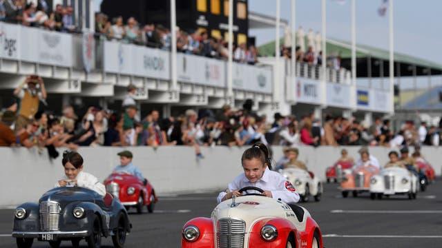 Kinders neem deel aan die Settrington Cup Pedal Car Race terwyl motorliefhebbers die Goodwood Revival bywoon, 'n driedaagse historiese motorrenfees in Goodwood, Chichester,