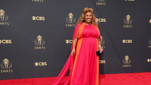 Ashley Nicole Black wears a flowing orange and pink gown at the 2021 Emmy Awards
