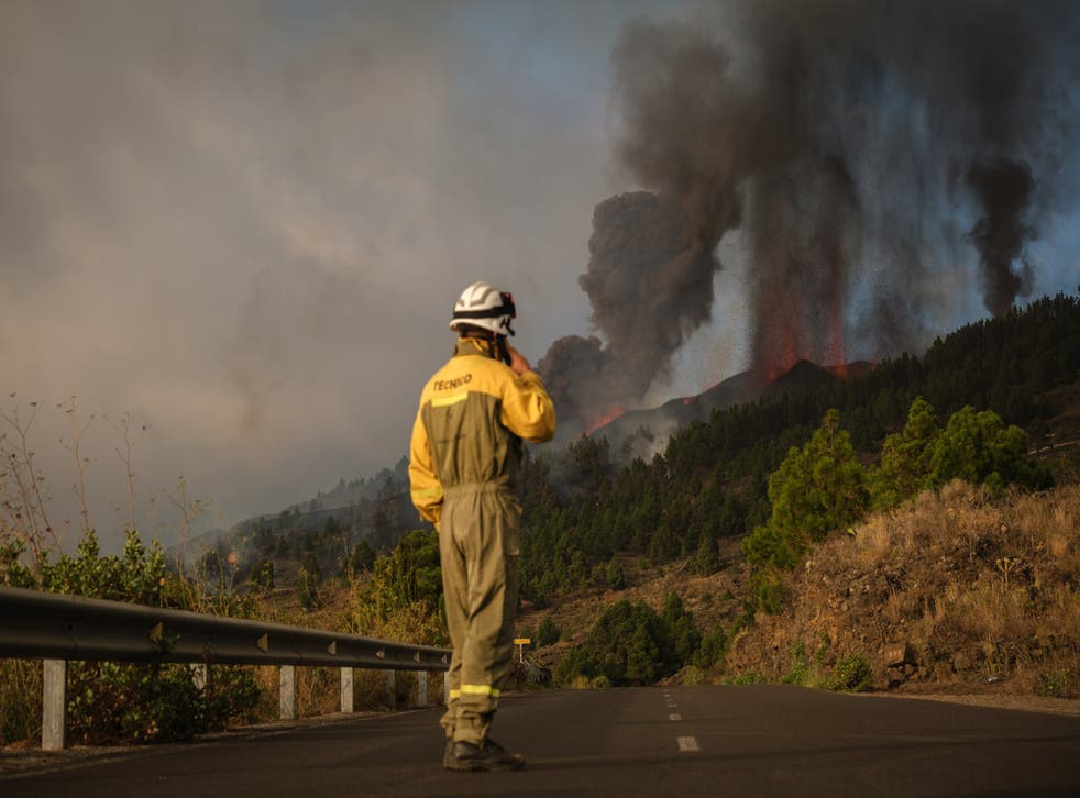 <p>Firefighters at the scene as smoke billows from the volcano</s>