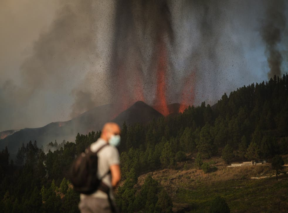 <p>A masked man watches on as lava spews from the volcano</s>