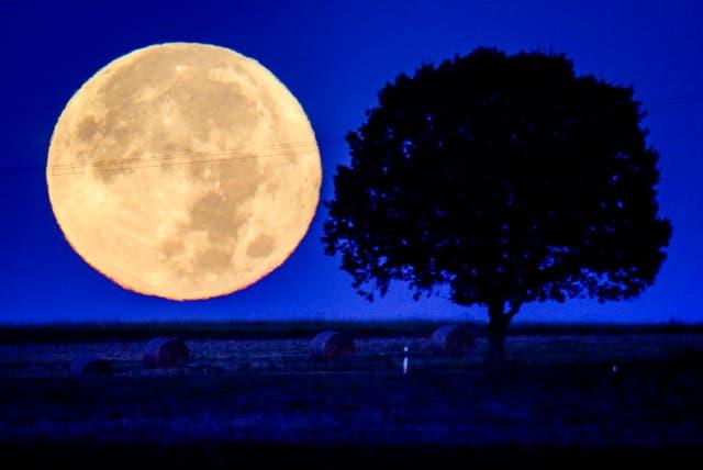 The full moon sets behind the hills of the Taunus region near Wehrheim, Germany