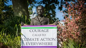 A new sign hangs on the Millicent Fawcett statue after it was altered by 'CrackTheCrises' coalition activists to highlight the climate crisis as a feminist struggle in Parliament Square in London