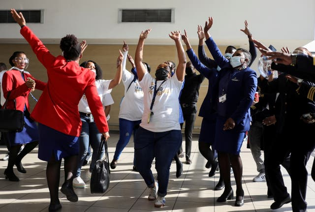 Workers sing and dance as a South African Airways airplane prepares to take off after a year-long hiatus triggered by the national airline running out of funds, at O R Tambo International Airport in Johannesburg