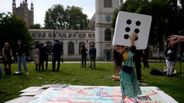 """Gabriella, the seven year old daughter of imprisoned British-Iranian Nazanin Zaghari-Ratcliffe, joins in a game on a giant snakes and ladders board in Parliament Square, to show the """"ups and downs"""" of her mother's case to mark the 2,000 days she has been detained in Iran"""