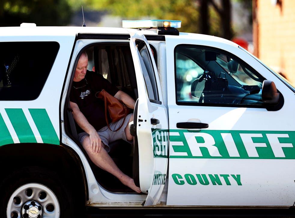 <p>Un homme est assis dans le véhicule du shérif après la fusiplade </p>
