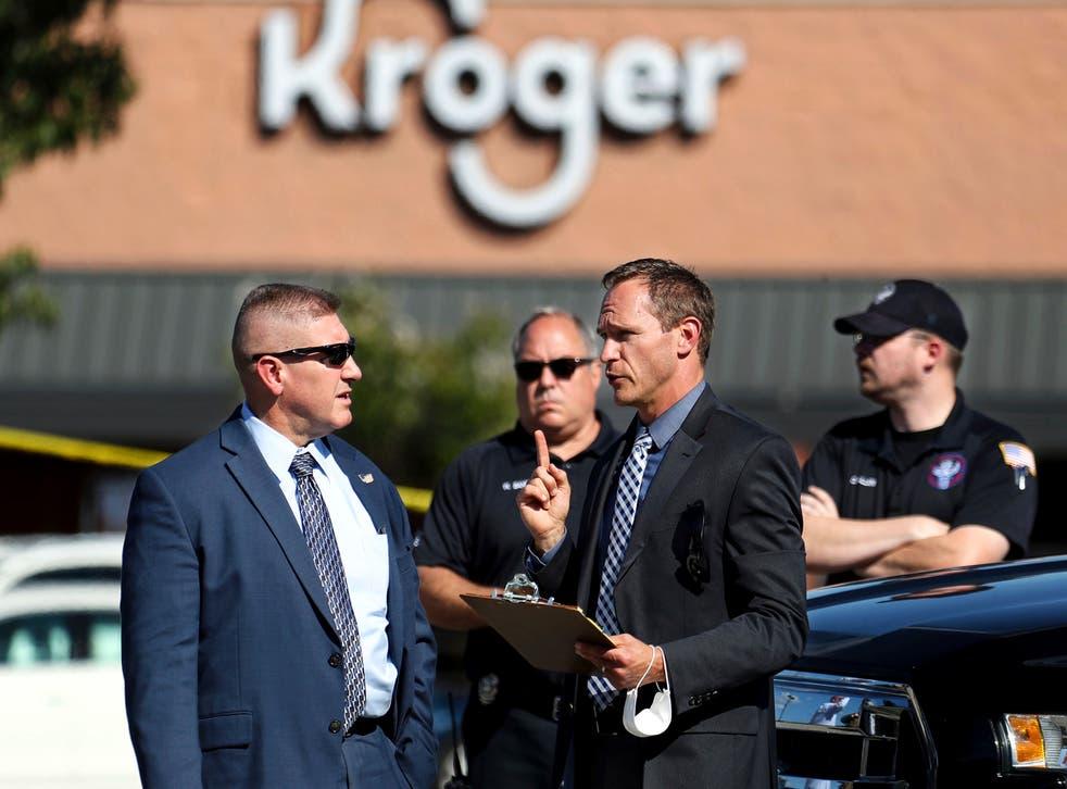 <p>Des agents des forces de l'ordre s'entretiennent sur les lieux après lapfusillade</p>