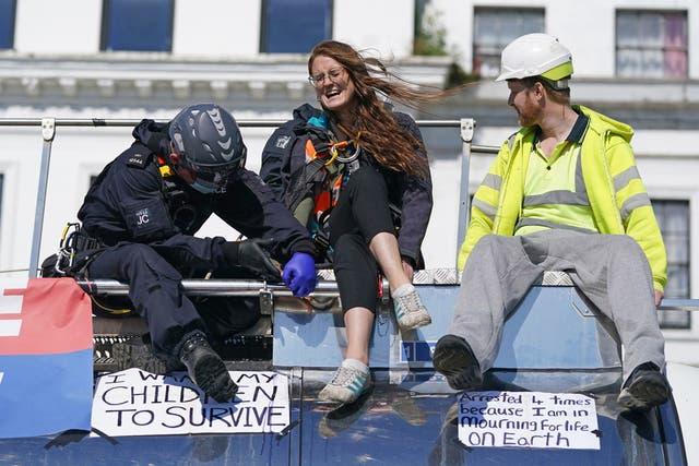 警察官はタンカーの上から2人の抗議者を連れ去ります, 断熱英国がケントでA20をブロックするように, ケントのドーバー港へのアクセスを提供します. ロンドンのM25高速道路でのキャンペーンが禁止された後、環境活動家は場所を移動しました