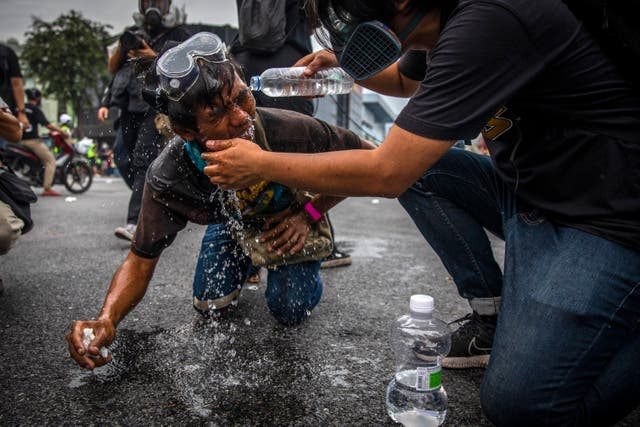 Thai anti-government protesters have their eyes flushed out after being teargassed by police during a rally in Bangkok, Thailand