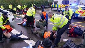 警察官は、M25高速道路からロンドンのヒースロー空港につながるラウンドアバウトを占領している英国の断熱材から抗議者を拘留します