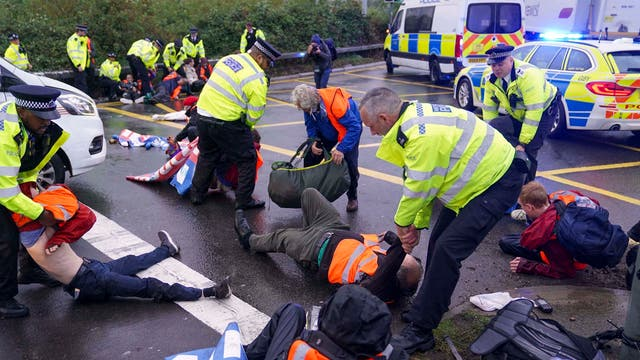 Police officers detain a protester from Insulate Britain occupying a roundabout leading from the M25 motorway to Heathrow Airport in London