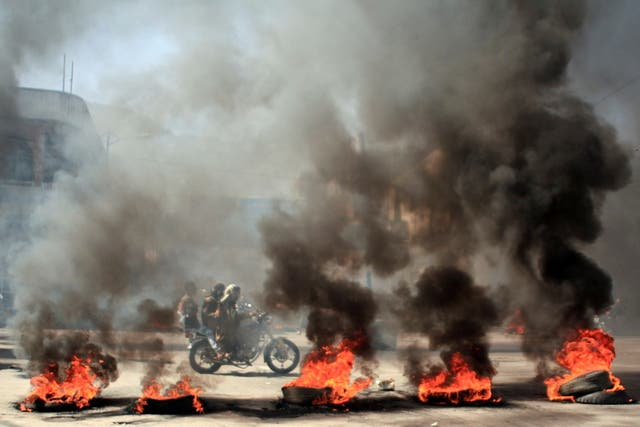 People ride a motorcycle past burning tires during protests against the deteriorating economic situation and the devaluation of the local currency, in Taiz, Yemen