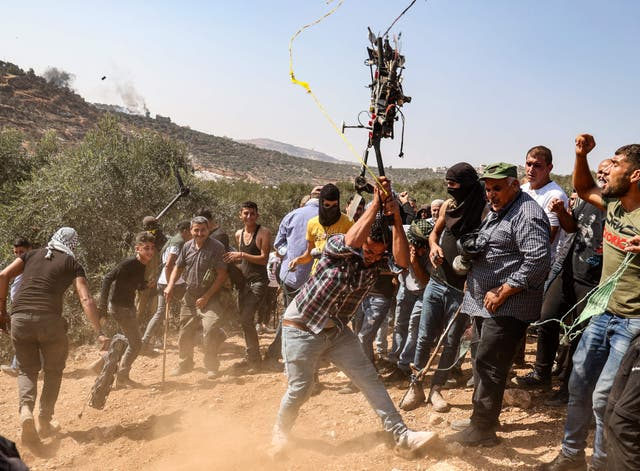 A Palestinian protester smashes an Israeli drone that reportedly fell because of a technical failure, during a demonstration against settlements in the West Bank village of Beita