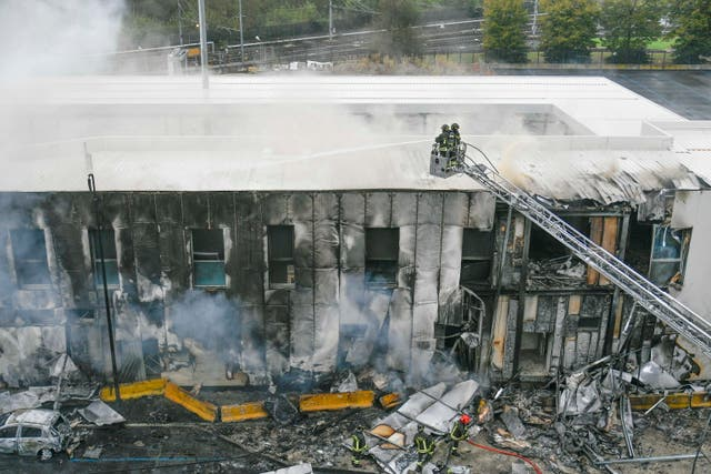 Firefighters work in a building that was crashed into by a small private plane in the San Donato Milanese district of Milan