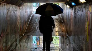 A couple make their way through a flooded underpass in Bristol as a yellow weather warning for rain and wind is issued for parts of the UK