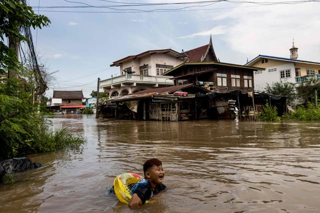 A boy wears a float as he swims in floodwaters in a neighbourhood in Ayutthaya, after tropical storm Dianmu caused flooding in 31 provinces across Thailand