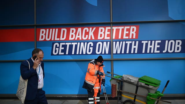 A delegate passes a street cleaner on the second day of the annual Conservative Party Conference being held at the Manchester Central convention centre