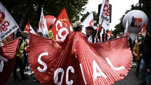 """A woman holds a banner reading """"Social"""" as people take part in a demonstration called by French unions as part of a nation-wide day for better working conditions"""