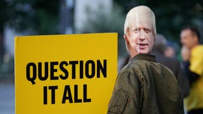 A protester, wearing a mask of Johnson, holds a sign reading 'Question it all' on the final day of the Tory conference