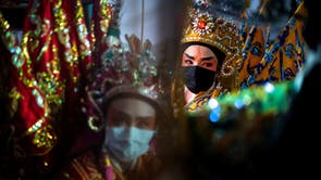 Members of a Chinese opera troupe wearing protective masks prepare before performing at a shrine during the annual vegetarian festival in Bangkok, Thailand
