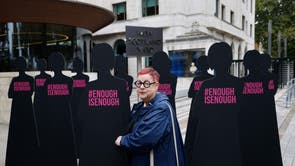British comedian Jo Brand poses with cut-out silhouettes representing women outside the Metropolitan Police headquarters New Scotland Yard, to highlight violence against women by male police officers or former police officers