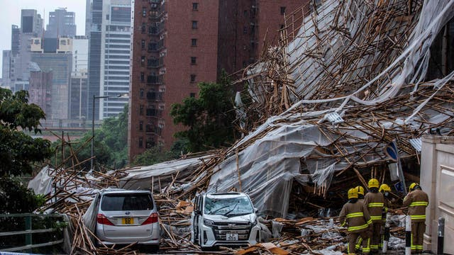Rescue personnel at the scene where bamboo scaffolding by a high-rise residential building collapsed onto a road, following strong winds and heavy rain from weather patterns from a tropical storm, in Hong Kong