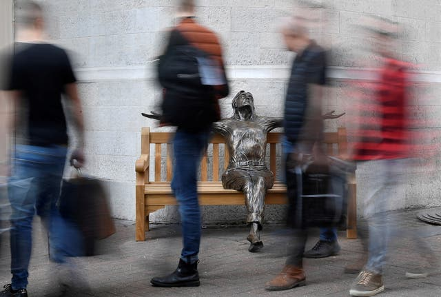"""People walk past a life-size sculpture of British singer John Lennon entitled """"想像"""", by sculptor Lawrence Holofcener, displayed to mark what would have been the 81st birthday for the former member of the Beatles in Carnaby Street"""