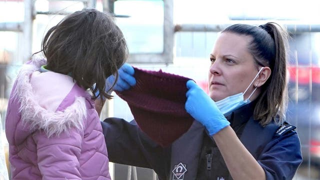 A young girl is helped by a Border Force officer as a group of people thought to be migrants are brought in to Dover, Kent, following a small boat incident in the Channel.