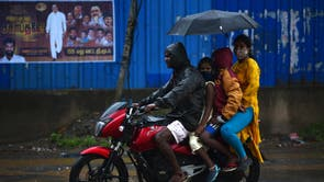 An Indian family rides on a motorcycle as they protect themselves with an umbrella during heavy rain, in Chennai, India
