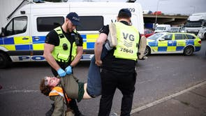 Police officers detain a man as Insulate Britain activists block a roundabout at a junction on the M25 motorway during a protest in Thurrock