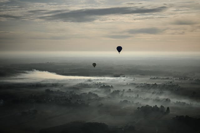 Hot air balloons fly over a forest at sunrise in the area of Saint-Emilion, southern France