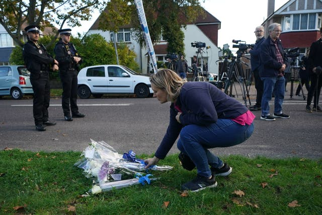 A person lays flowers at the scene near the Belfairs Methodist Church in Eastwood Road North, リーオンシー, エセックス, where Conservative MP Sir David Amess has died after he was stabbed several times at a constituency surgery. A man has been arrested and officers are not looking for anyone else
