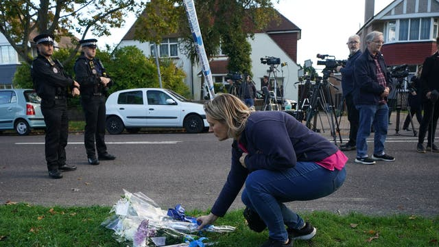 A person lays flowers at the scene near the Belfairs Methodist Church in Eastwood Road North, Leigh-on-Sea, Essex, where Conservative MP Sir David Amess has died after he was stabbed several times at a constituency surgery. A man has been arrested and officers are not looking for anyone else