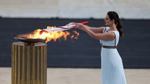 Flame handover ceremony in Athens for the Beijing 2022 Winter Olympics, Panathenaic Stadium, 雅典. Greek actress Xanthi Georgiou, playing the role of High Priestess lights the torch with the flame during the ceremony