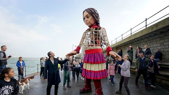 Actor Jude Law holds hands with Little Amal, a 3.5-metre-tall puppet of a nine-year-old Syrian girl, as it arrives in Folkestone, Kent, as part of the Handspring Puppet Company's 'The Walk'