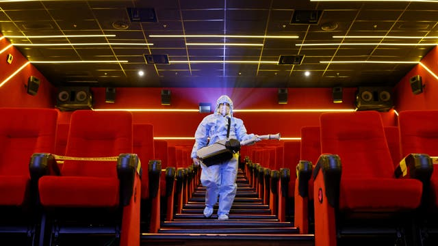 A worker wearing personal protective equipment sanitises seats inside a movie theatre ahead of its reopening in Mumbai, 印度