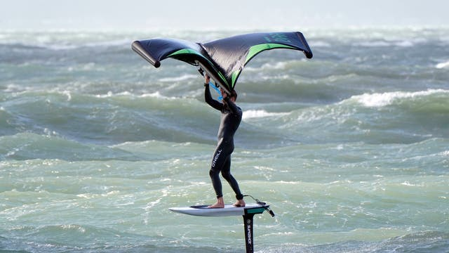 A wing surfer enjoys the strong winds as they surf in the sea off of Hayling Island in Hampshire