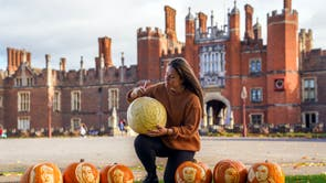 Palace Gardener Justine Howlett adds the finishing touches to pumpkins bearing the face of Henry VIII and his wives, at Hampton Court Palace.