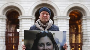 Richard Ratcliffe holds up a photo of his wife Nazanin Zaghari-Ratcliffe as he protests outside the Foreign Office while on hunger strike, part of an effort to lobby the UK foreign secretary to bring his wife home from detention in Iran