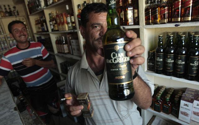 A shop-owner brandishes a bottle of whisky in Baghdad, where drink stores have reopened