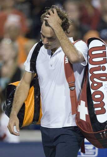 Roger Federer walks off court after losing to Gilles Simon at the Toronto Masters. Rafael Nadal, Federer's conqueror at Wimbledon, is now close to taking over as world No 1