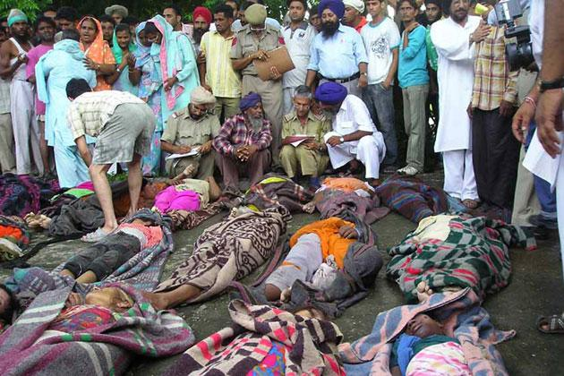 Indian Punjab police and villagers surround the dead bodies of devotees at the Civil Hospital in Anandpur Sahib