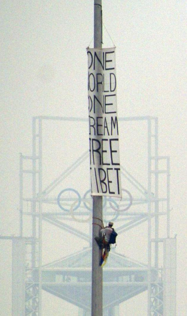A protester beat the security cordon to hang a banner that read 'One World One Dream Free Tibet' near the Olympic Green