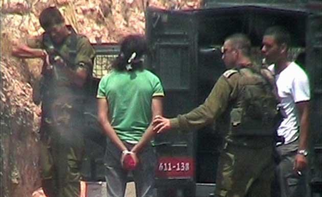 Lt-Col Omri Burberg holds the handcuffed and blindfolded Palestinian man and orders a soldier to shoot